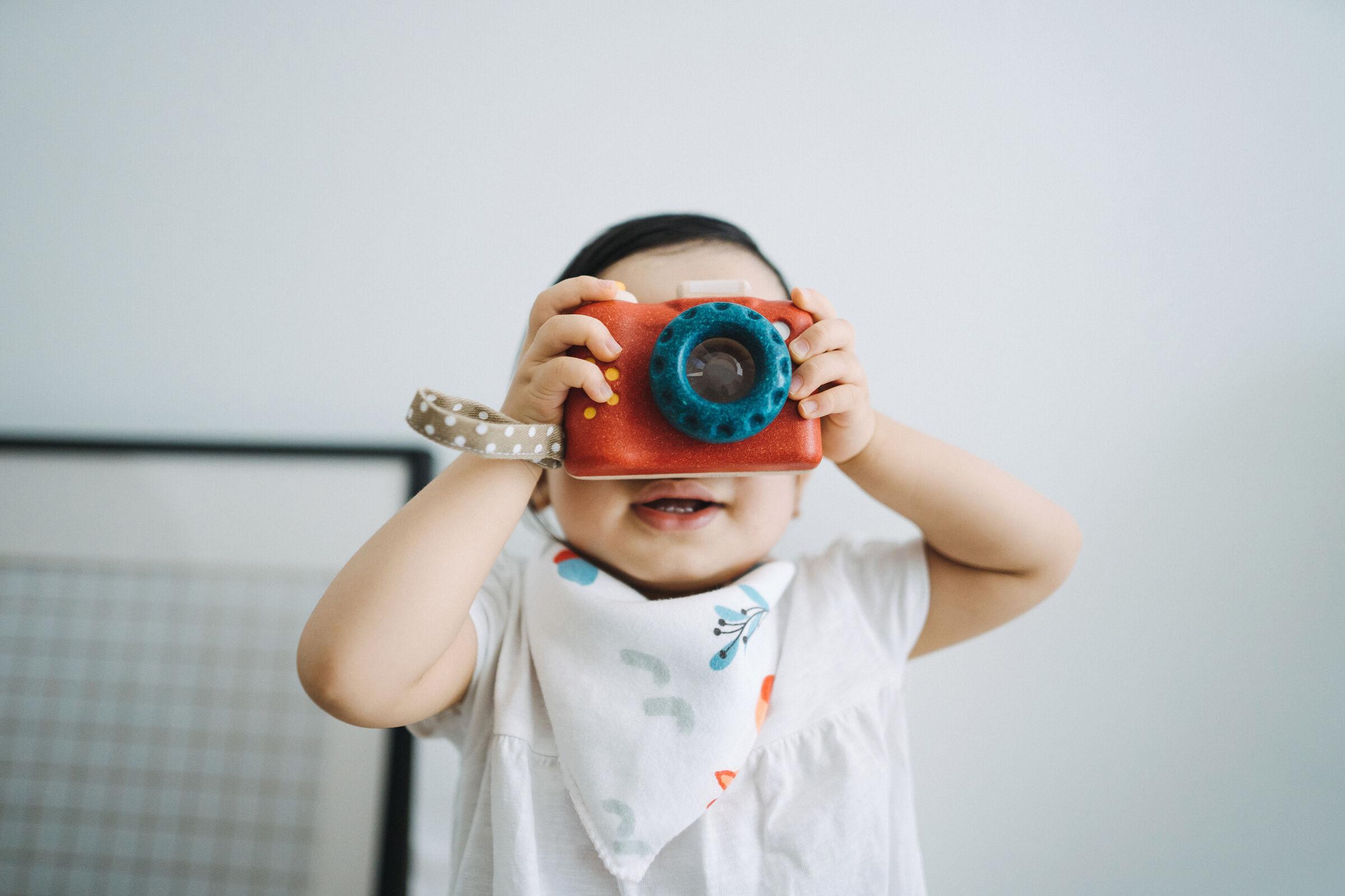 Criança-segurando-uma-maquina-fotografica-de-brinquedo