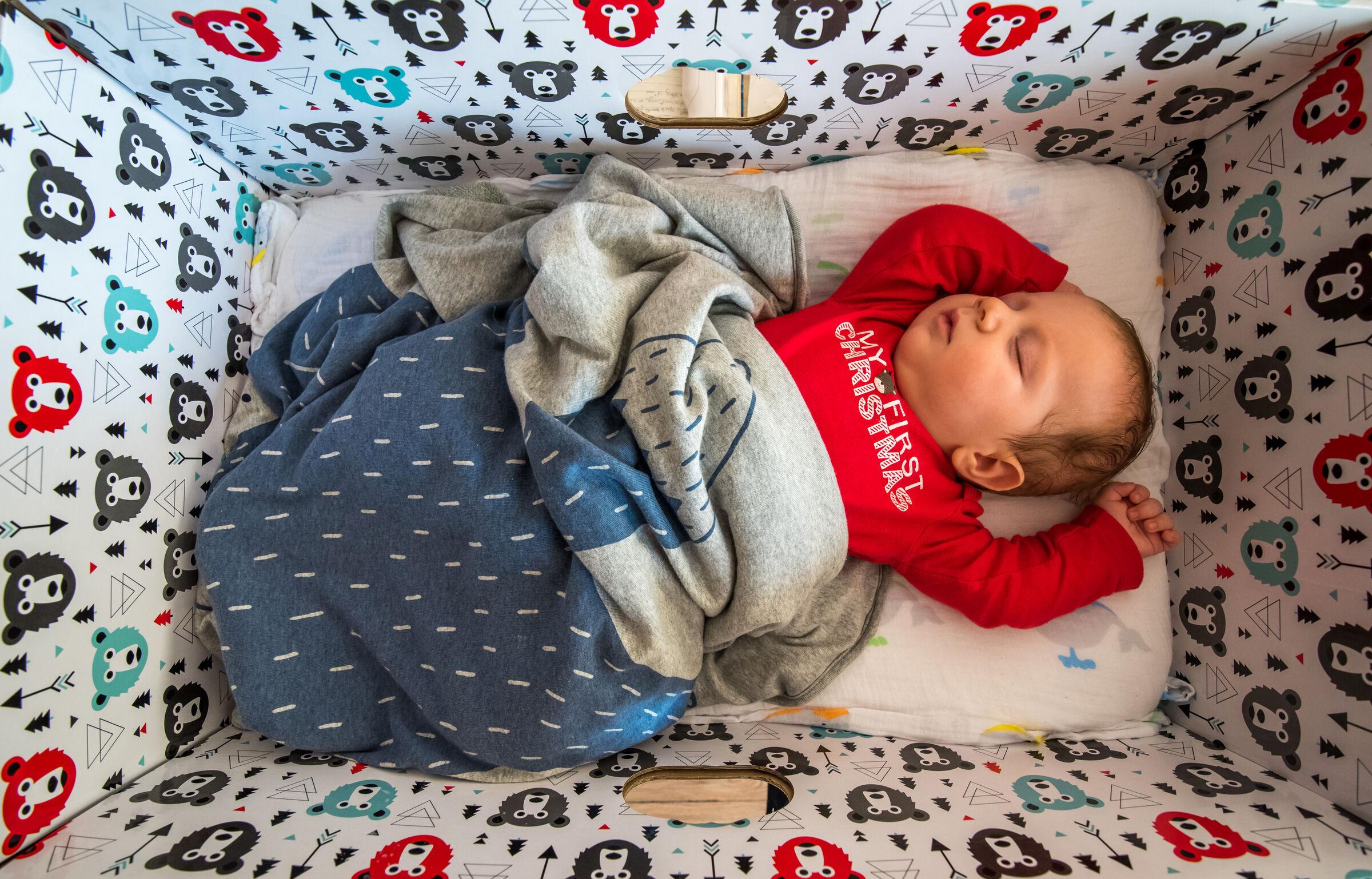Bebê-dentro-do-berço-feito-de-caixa-de-papelão
