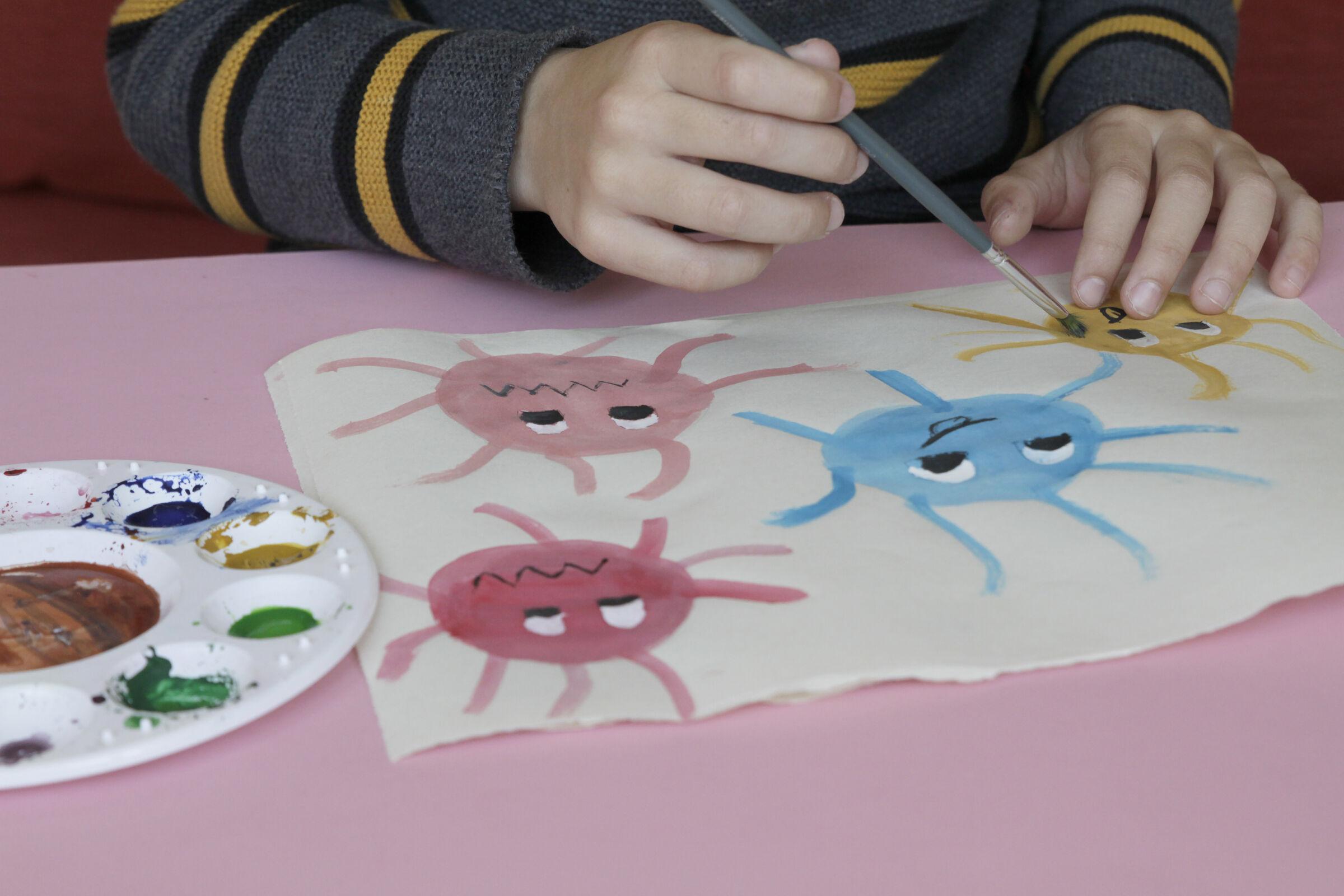 Garoto-pintando-desenhos-de-coronavirus