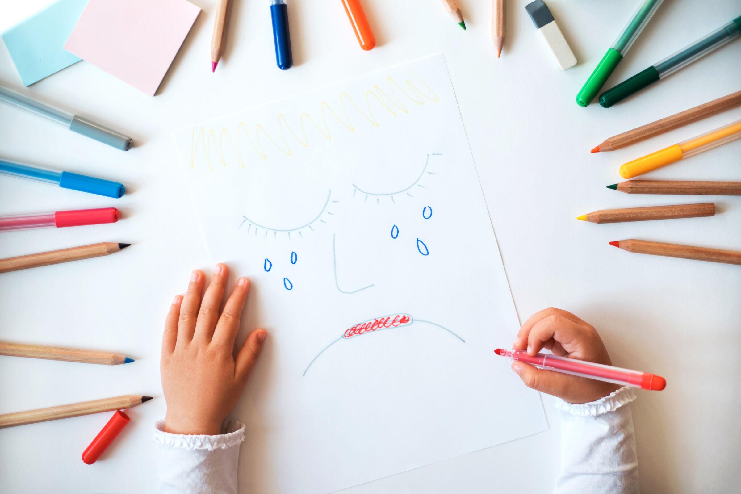 Criança-segurando-um-desenho-com-rosto-triste