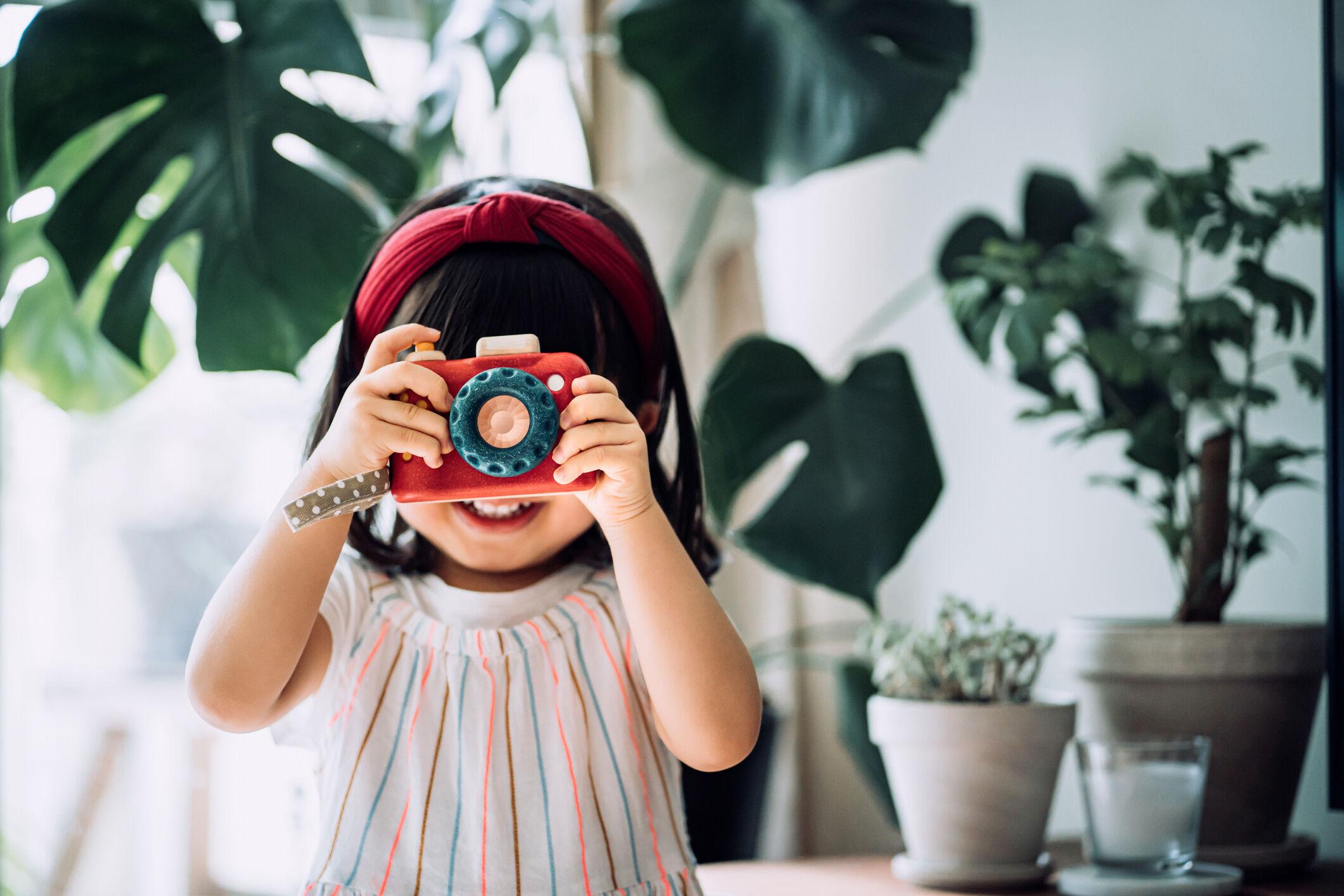 Menina com câmera de brinquedo