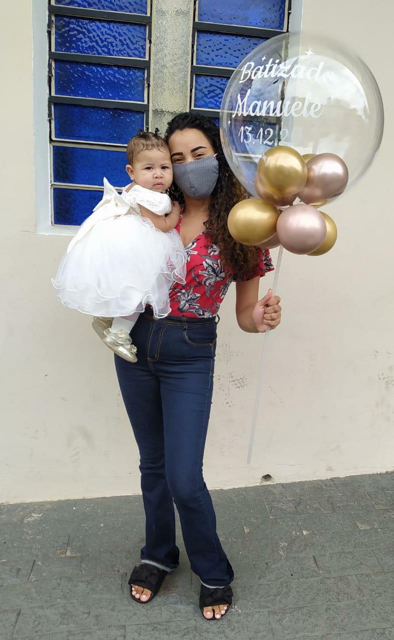 mãe segurando bebê e balão