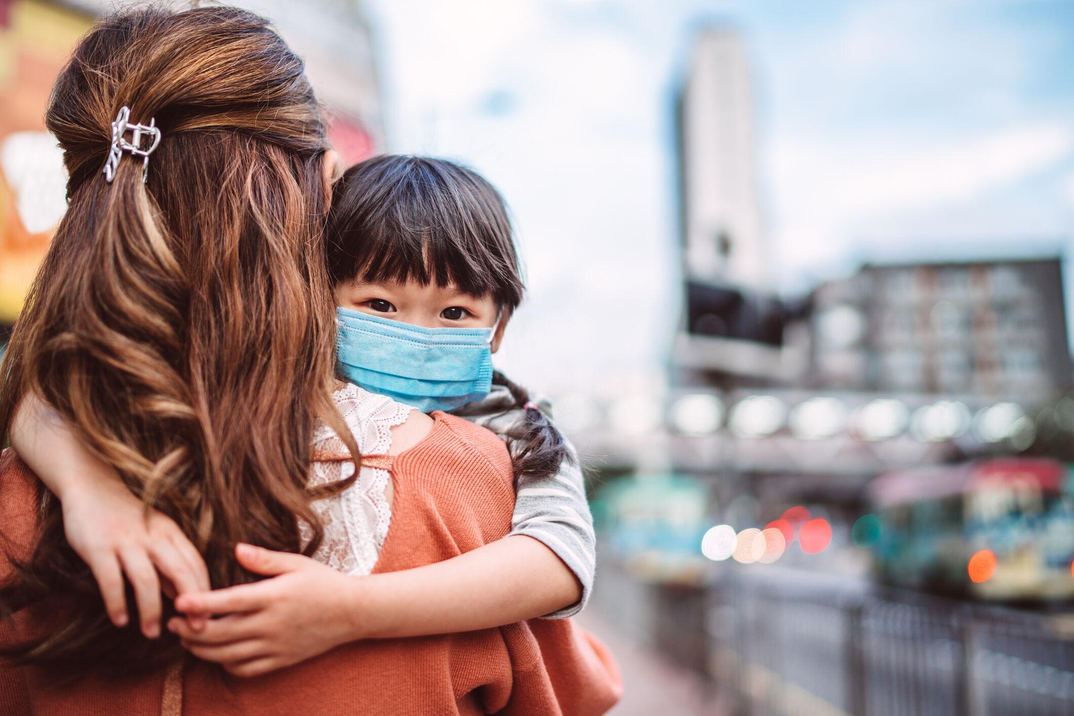 Mulher de costas carregando criança usando máscara