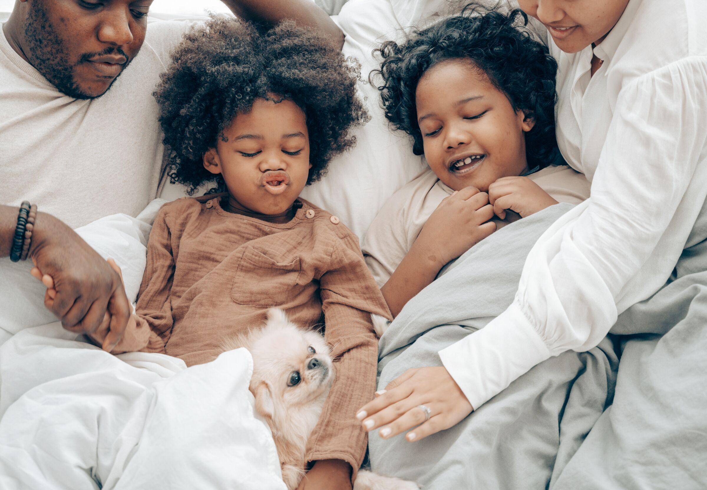 Família deitada na cama com cachorro