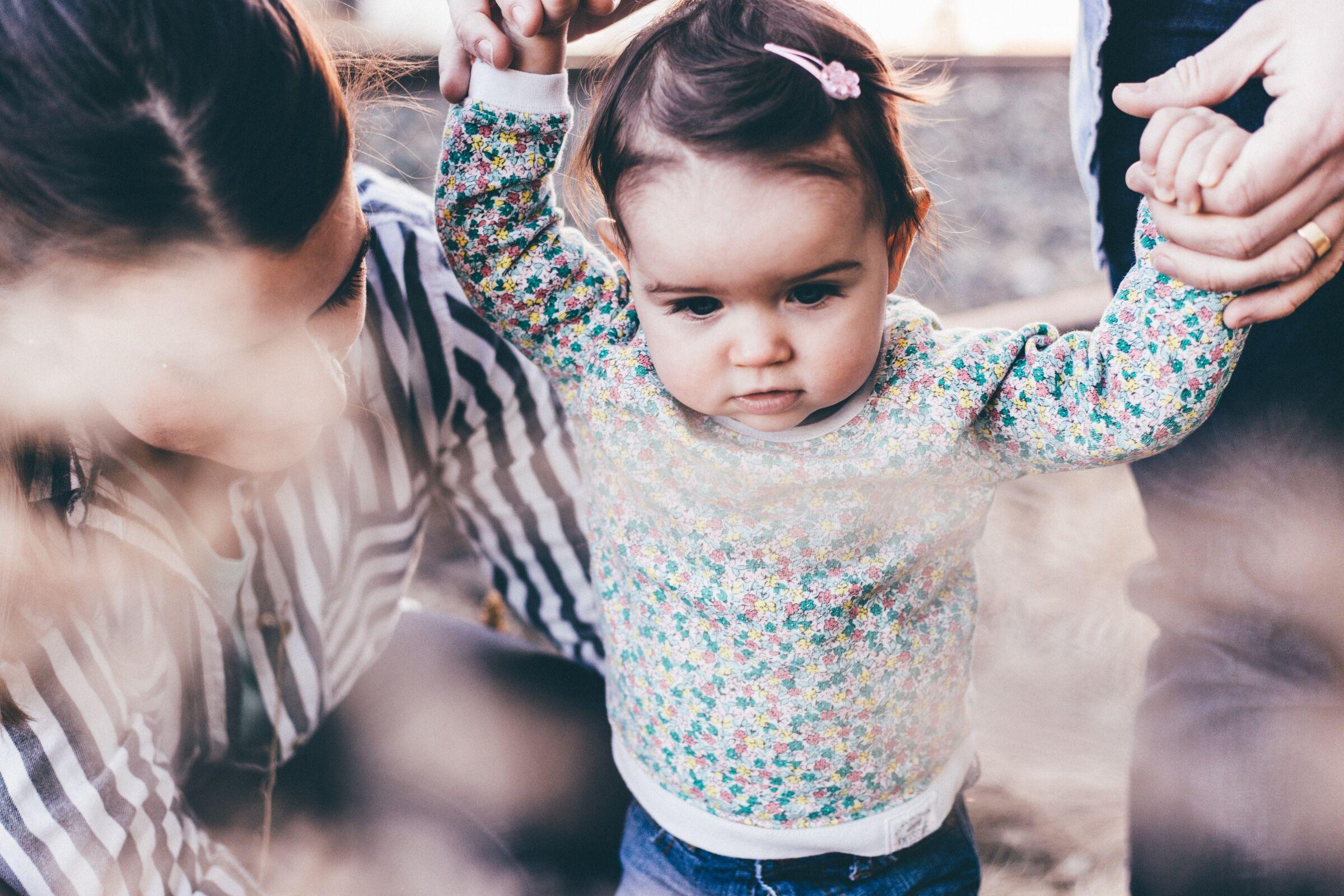 Pais-ajudando-filha-a-dar-os-primeiros-passos