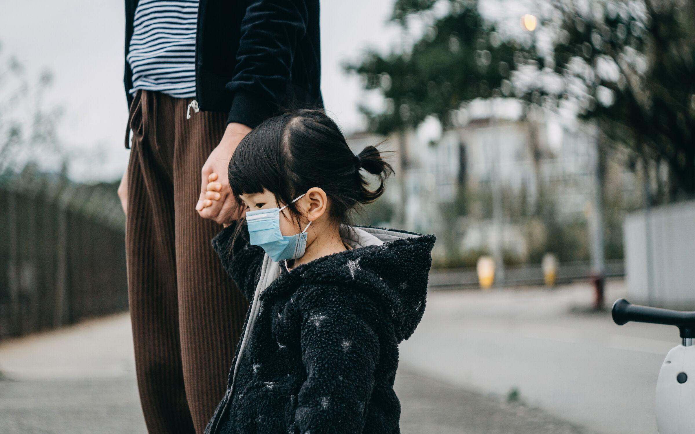 Mãe-atravessando-a-rua-com-a-filha-usando-mascara