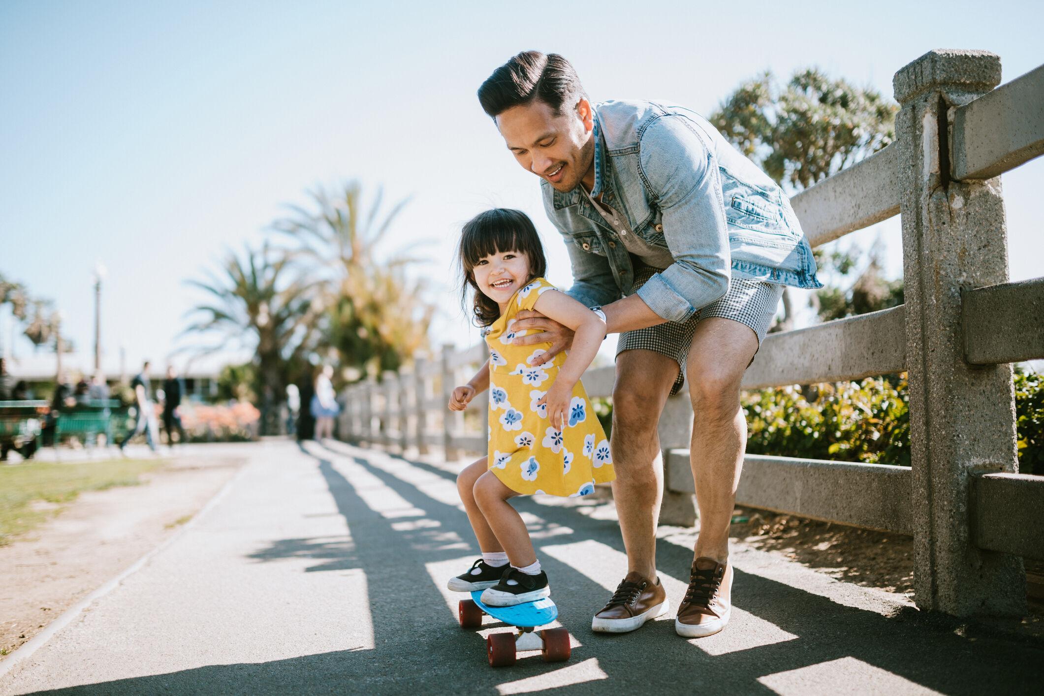 Pai ajudando a filha a andar de skate