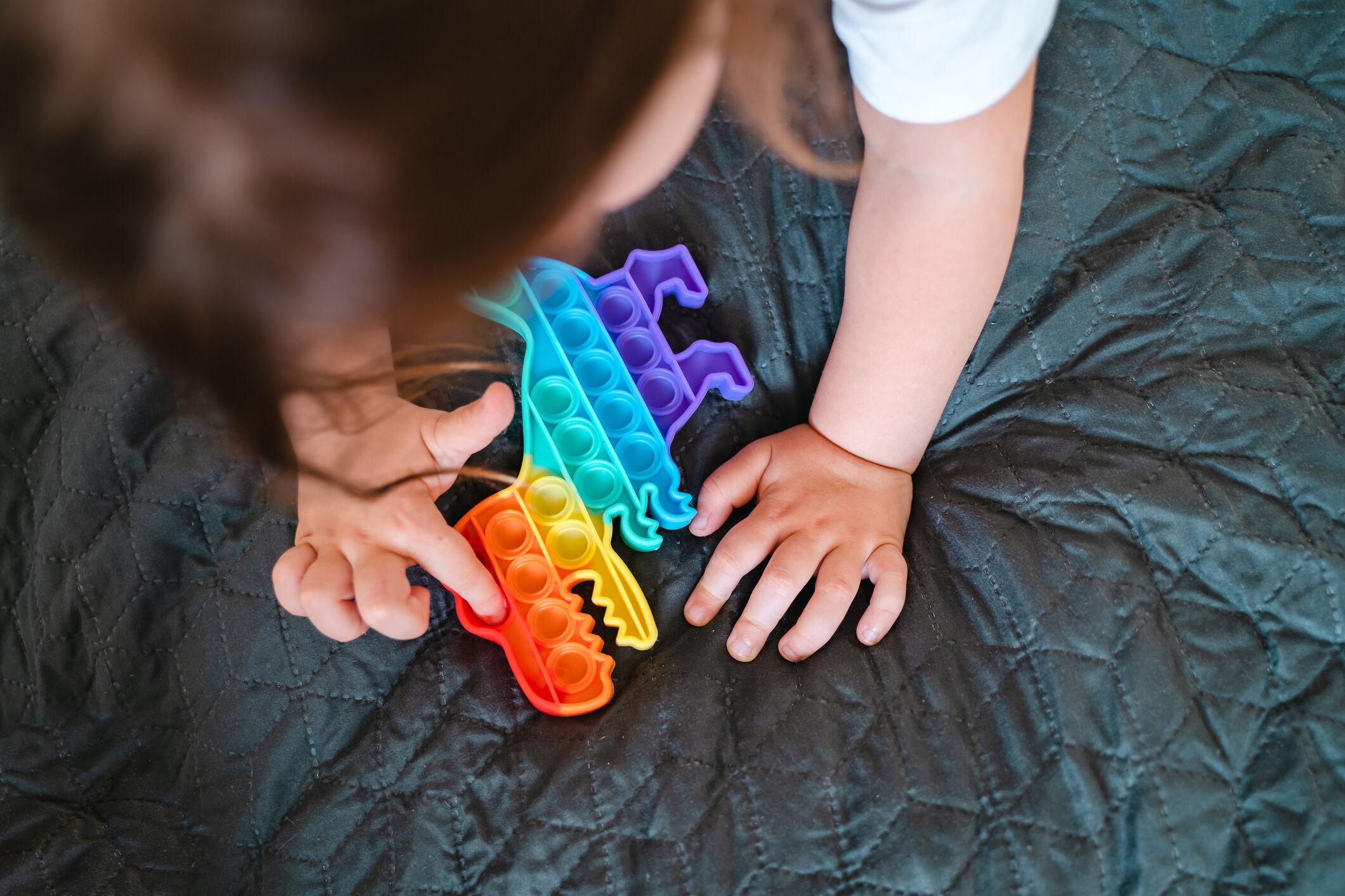 Criança brincando com Push Pop It