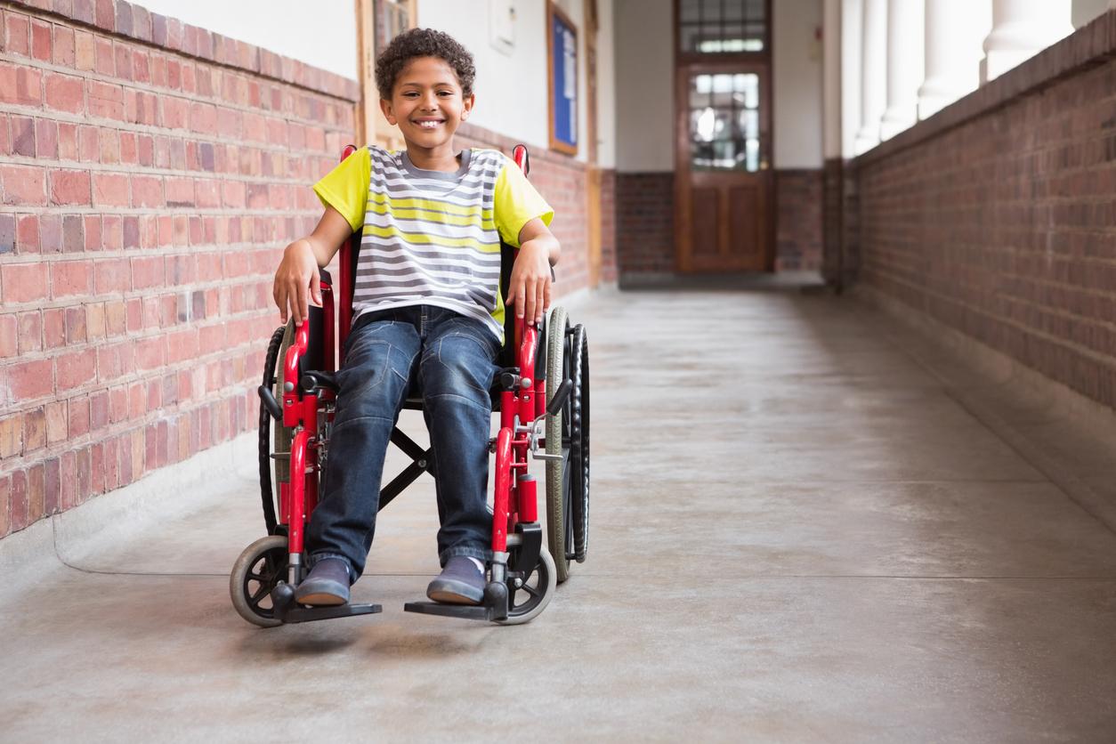 Menino usando cadeira de rodas enquanto sorri para a câmera